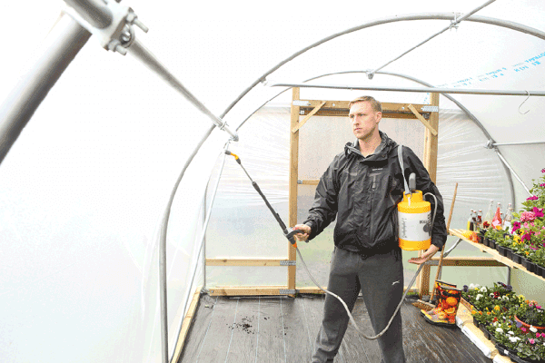 man cleaning the inside of a polytunnel