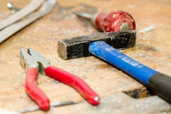 pliers a hammer and a screwdriver on a workbench