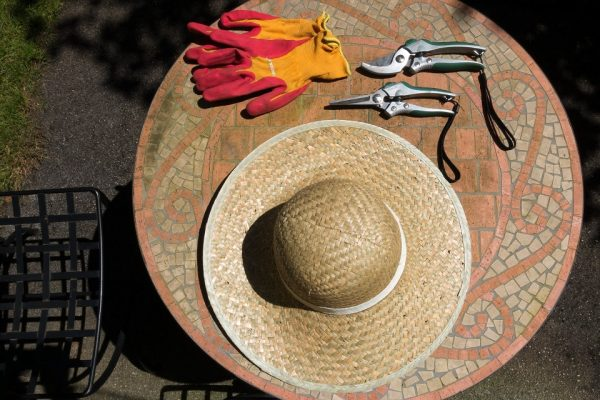 gardening tools and a sunhat on a round table