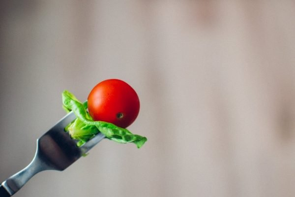 lettuce and a cherry tomato on a fork