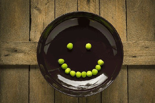 black plate with peas arranged in a smile