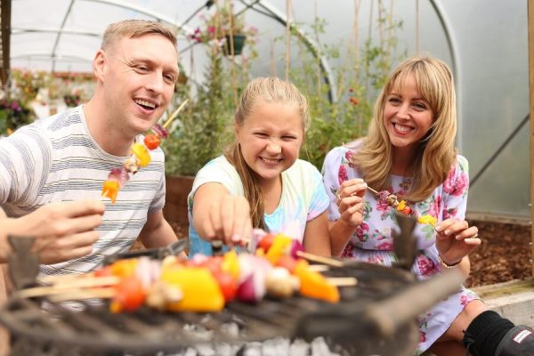 family sat by a polytunnel eating food cooked in their garden